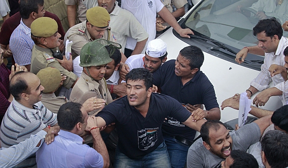 Police try to remove supporters of Hazare who were attempting to block the vehicle carrying Hazare after he was arrested by police in New Delhi on August 16, 2011