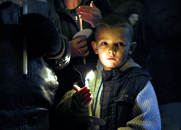 Five year old Jason Ward holds a candle alongside other children during the vigil at Salford