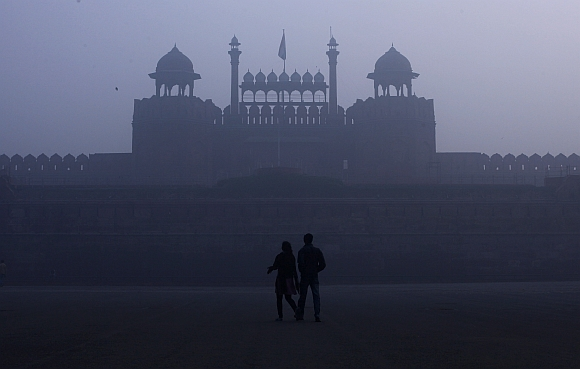 A couple walks in front of the Red Fort amid dense fog on a cold winter morning in the old quarters of Delhi