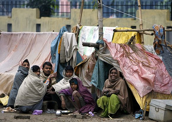Homeless people sit outside their makeshift tents in Bihar