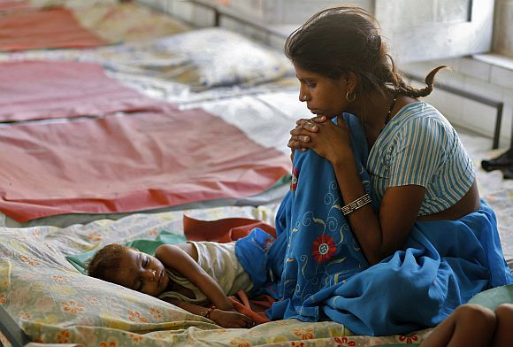 A mother looks at her malnourished child in a hospital in Bhopal