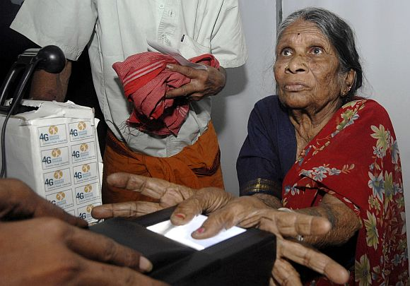 File picture of a woman undergoing the process of a fingerprint scanner during UID database system in a village in Andhra Pradesh