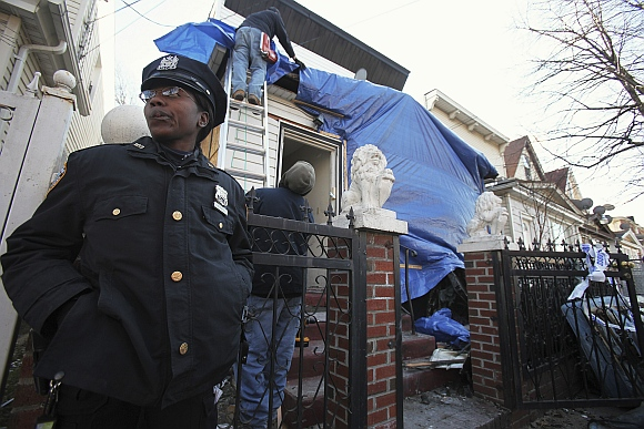 A New York City police officer stands outside a residence that was hit by a firebomb in the Queens borough of New York.