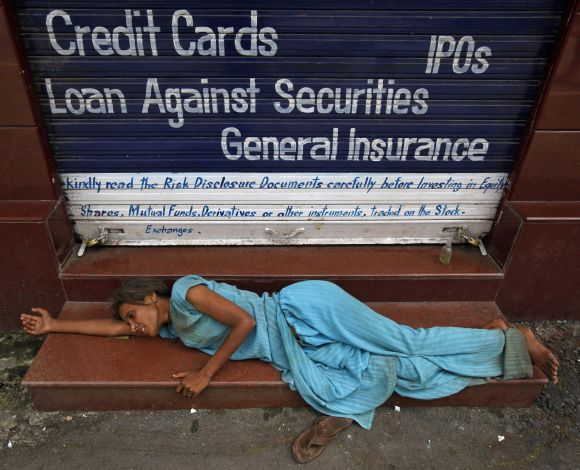 A homeless woman sleeps on the stairs of a closed brokerage office in Mumbai