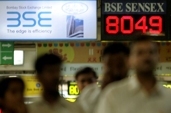 Indian commuters walk past electronic board displaying Bombay Stock Exchange's index at railway station in Mumbai.