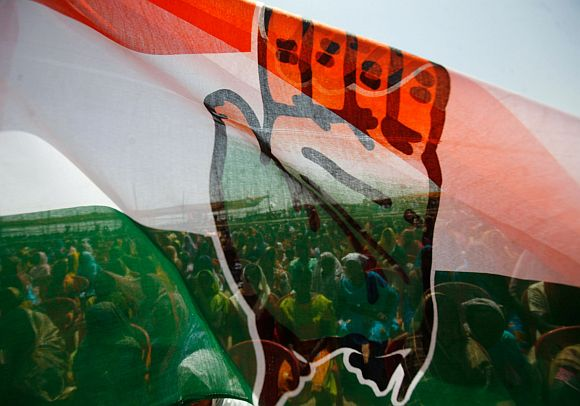 People attending election campaign rally are seen through Congress flag in West Bengal