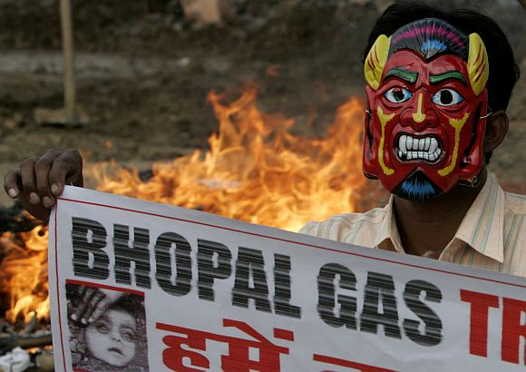 An activist wearing mask holds banner during a protest against the Bhopal gas disaster verdict in Bhopal