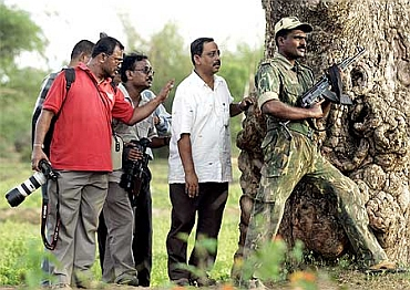 Media personnel and a police officer take cover behind a tree during a firefight between police and Maoists