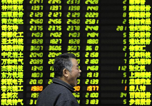 An investor yaws as he walks past an electrical board showing stock information at a brokerage house in Nanjing, China
