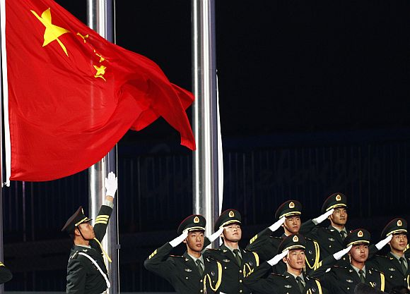 Soldiers salute as they raise China's national flag during a ceremony in Guangzhou