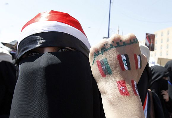 An anti-government protester displays paintings on her hand in Sanaa, Yemen