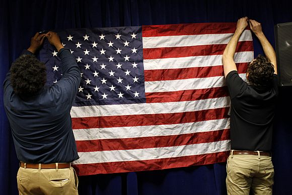 Volunteers hang an American flag before a US Presidential candidate's campaign town hall meeting in Concord