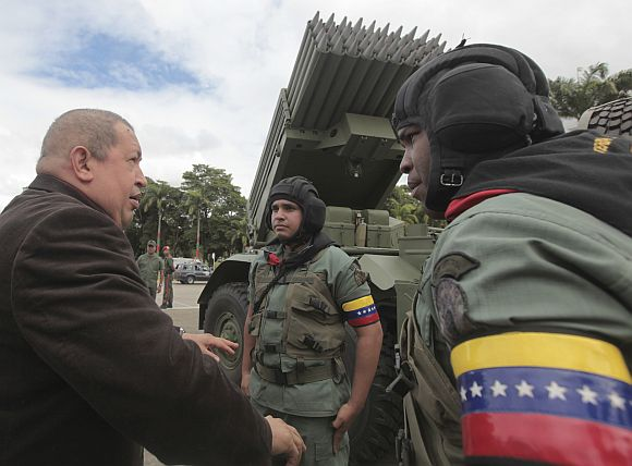 Venezuela's President Chavez talks to soldiers during a ceremony at the military academy in Caracas