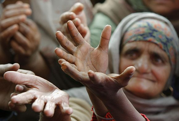 People raise their hands to receive food from a roadside charitable community kitchen, on the outskirts of Jammu