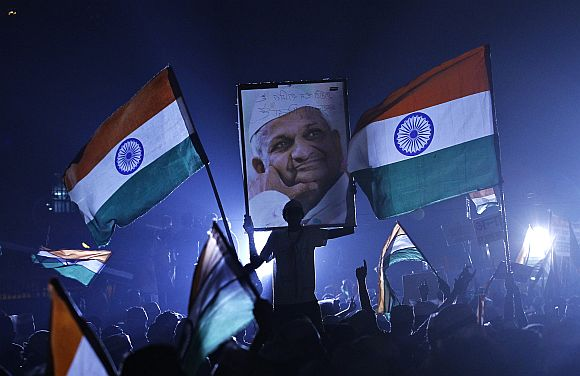 A supporter of Anna Hazare holds his portrait during his fast at Ramlila grounds in New Delhi in this file picture