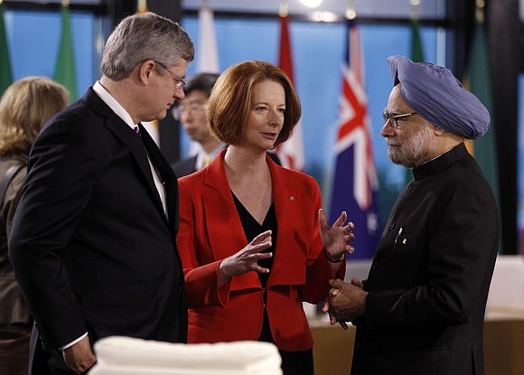 Australia's Prime Minister Julia Gillard speaks with Canada's Prime Minister Harper and PM Singh before a meeting on the second day of the G20 Summit in Cannes