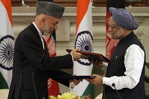 Afghanistan's President Karzai and PM Singh exchange documents after signing a joint statement at Hyderabad House in New Delhi