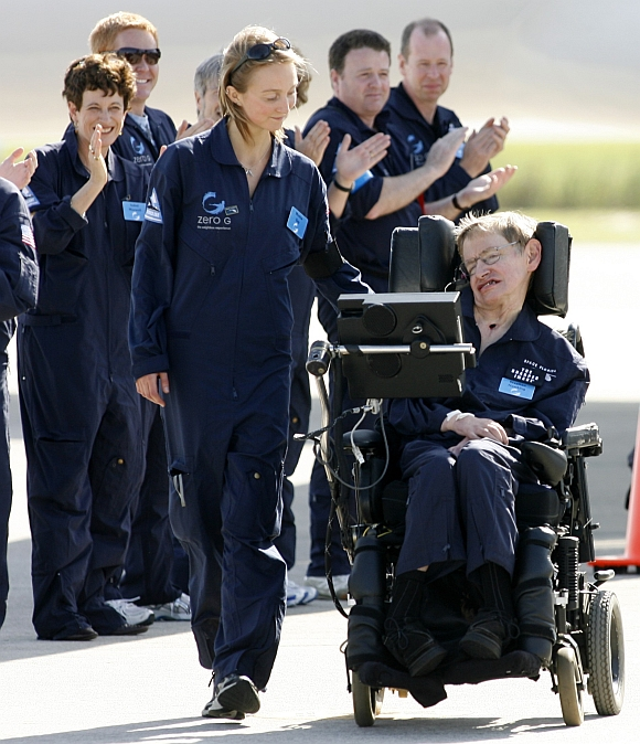 Hawking is wheeled by the people who took part in a ZERO-G flight with him at Kennedy Space Center in Cape Canaveral, Florida