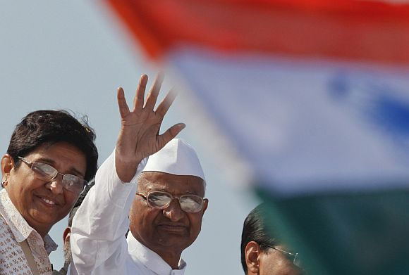Anna Hazare with Kiran Bedi wave from a vehicle during a rally in Mumbai