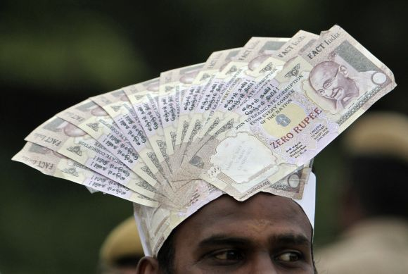 A supporter of social activist Hazare wears a cap lined with fake currency notes while attending a public meeting in Chennai