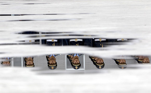 Soldiers from the honour guards of the Chinese People's Liberation Army are reflected in puddles of water