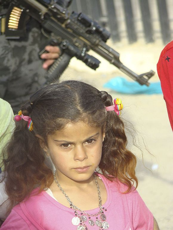 A girl stands near a policeman providing security in the city of Kut, 150 km (95 miles) southeast of Baghdad in this 2009 photo