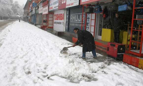 A man clears snow in front of his shop in Srinagar