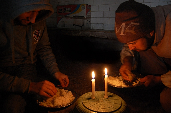 A Kashmiri family struggles to have its meal in candle light