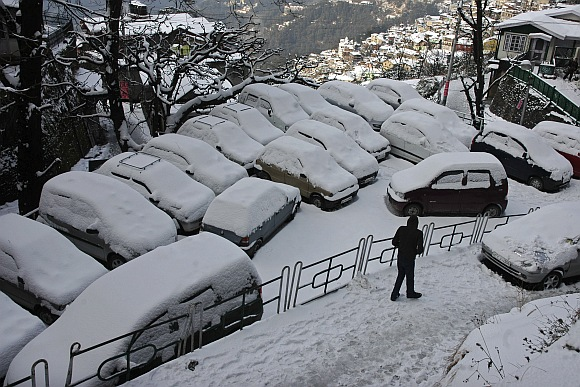 A man walks pasts snow covered cars after heavy snowfall in Shimla.