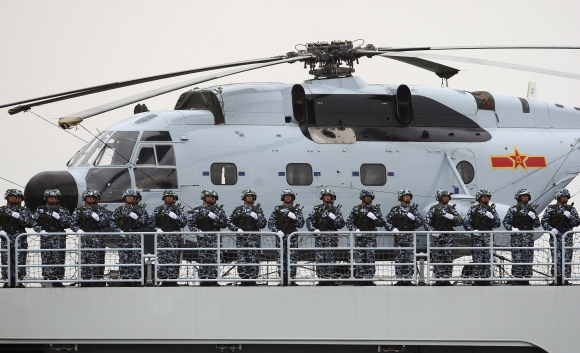 Chinese Marines stand at attention on a warship with a Changhe Z-8 helicopter