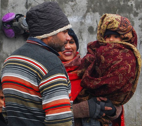 A tourist family wrapped in heavy winter wear is seen in Srinagar on Monday