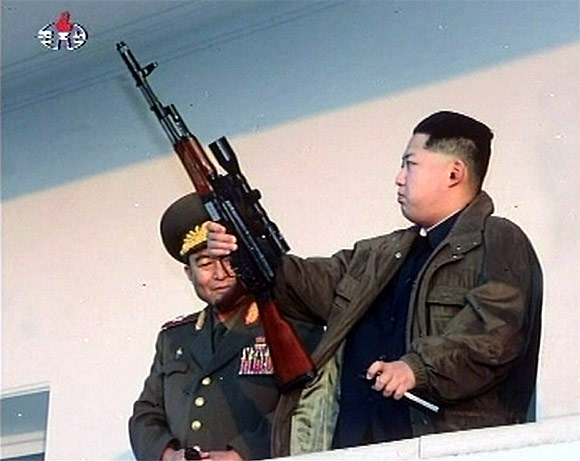 New leader of North Korea Kim Jong-un holds a weapon in this undated still image taken from video