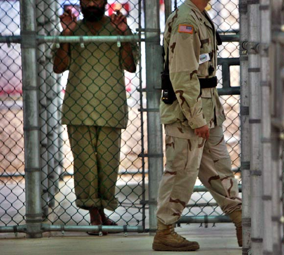 In this photo reviewed by US military officials, a detainee whose name, nationality, and facial identification are not permitted, holds onto a fence as a US military guard walks past the grounds of the maximum security prison at Camp 5 in the Guantanamo Bay