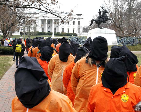 Protesters seeking the closure of the Guantanamo Bay detention facility wear orange jumpsuits and black hoods as they demonstrate outside the White House in Washington, DC