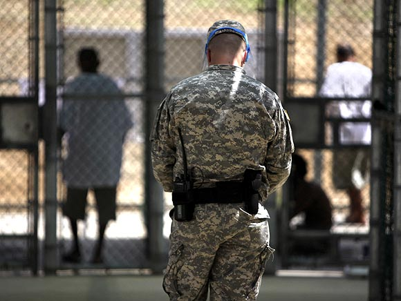 A guard watches over Guantanamo detainees inside the exercise yard at Camp 5 detention facility at Guantanamo Bay