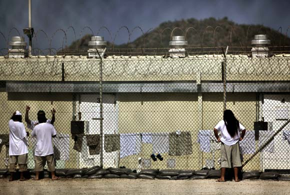 Detainees talk together inside the open-air yard at the Camp 4 detention facility at Guantanamo Bay