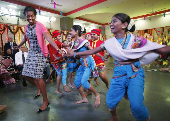 U.S. President Barack Obama and first lady Michelle Obama dance during their visit to the Holy Name High School in Mumbai