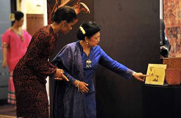 Michelle Obama tours an exhibition with Ani Yudhoyono, wife of Indonesia's President Susilo Yudhoyono, in Jakarta
