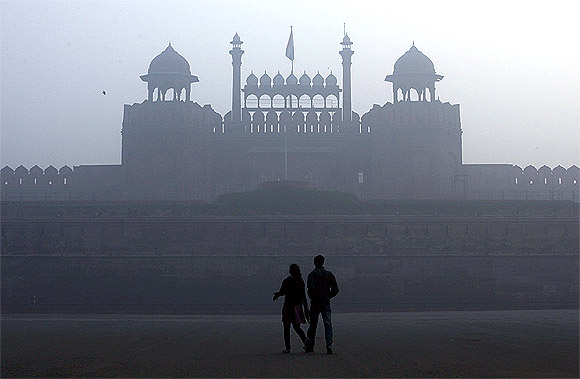 A couple walks in front of the historic Red Fort amid dense fog on a cold winter morning in the old quarters of Delhi