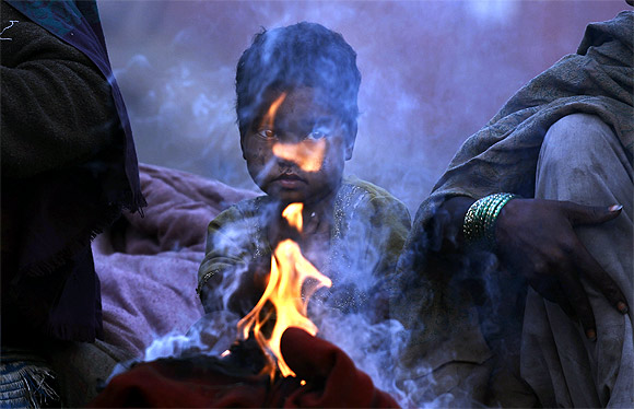 A child sits next to a fire to warm herself on a cold winter morning in the old quarters of Delhi