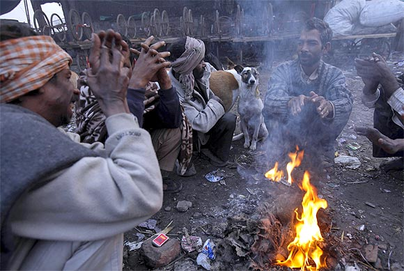 Men sit next to a dog around a fire to warm themselves on a cold winter morning in the old quarters of Delhi
