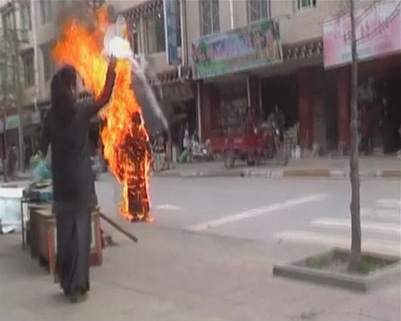 A woman throws a white scarf over Tibetan Buddhist nun Palden Choetso as she burns on the street in Daofu, or Tawu in Tibetan, in this still image taken from video shot on November 3, 2011