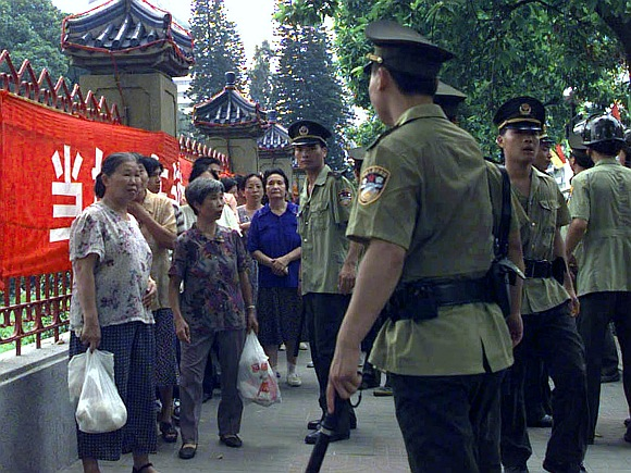 Chinese policemen confront suspected members of the Falun Gong sect during a protest in Guangzhou in this dated photograph