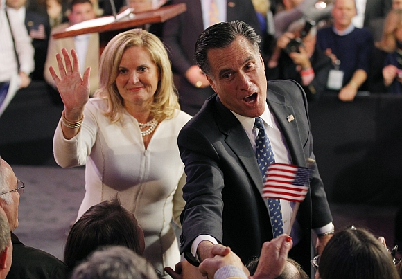 Romney shakes hands with supporters as his wife Ann waves after he spoke at his New Hampshire primary night rally
