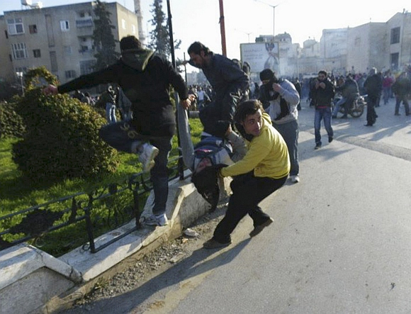 Anti-government protesters carry an injured man while covering their faces from tear gas being fired in Adlb