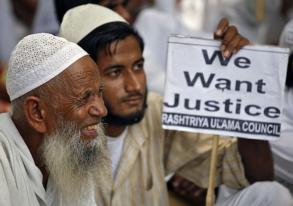 Members of Rashtriya Ulama Council hold a placard as they take part in a protest against what they call a fake encounter, in New Delhi