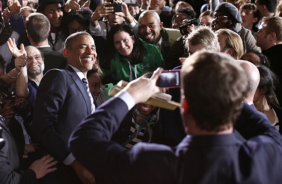 U S President Obama poses for a photo after speaking about jobs and the economy at Shaker Heights High School during a trip to Cleveland