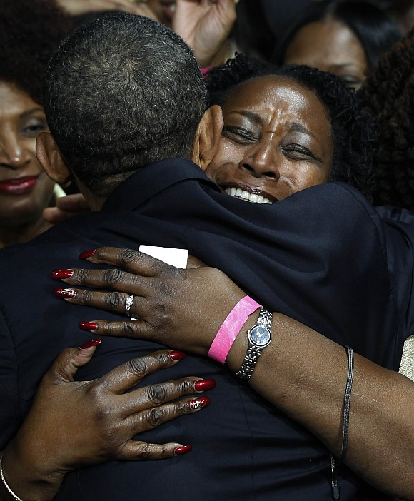 A supporter hugs U S President Barack Obama after his speech at a Chicago Forum event at the University of Illinois in Chicago