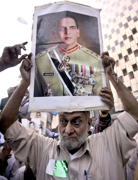 A man holds up a poster of Pakistan's army chief General Ashfaq Kayani