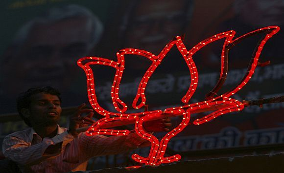 A BJP worker installs the party's election symbol on balcony of the party headquarters in Lucknow